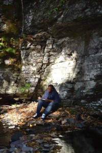 Corey sitting by the stream writing.
