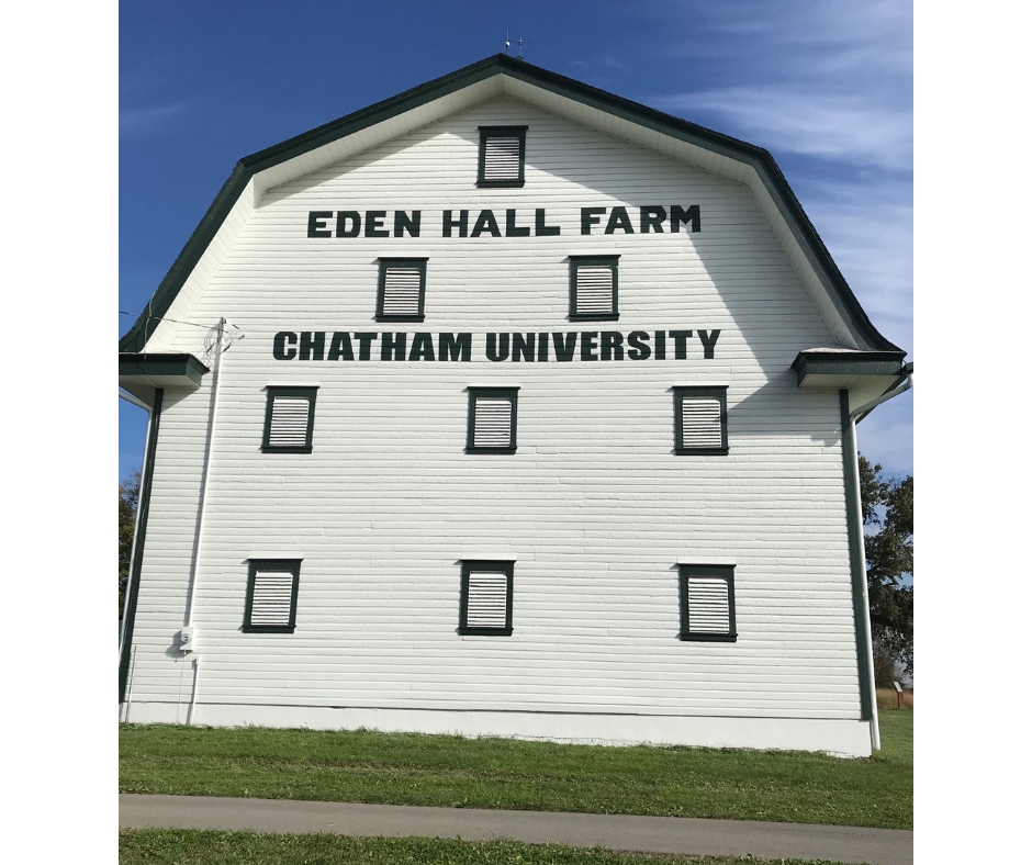 A white barn with a blue sky behind it. It sits on a plot of green grass. The barn has the words Eden Hall Farm Chatham University placed on it in block letters