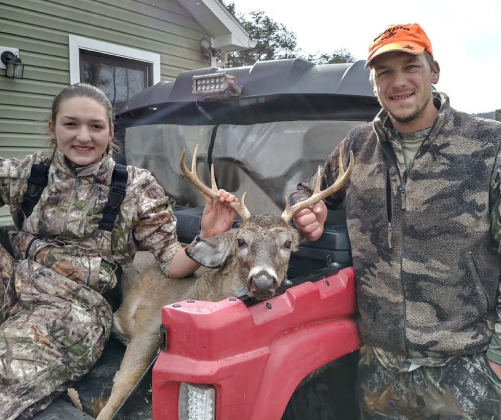A girl and man with a dead buck